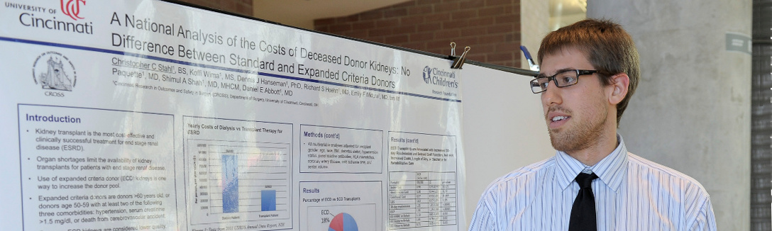 student in front of research display